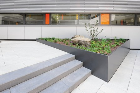 A set of three steps are harmoniously framed by the raised beds. Finished with a plastic coating in DB 703 iron mica, the beds create an appealing contrast with the light floor slabs in the courtyard.