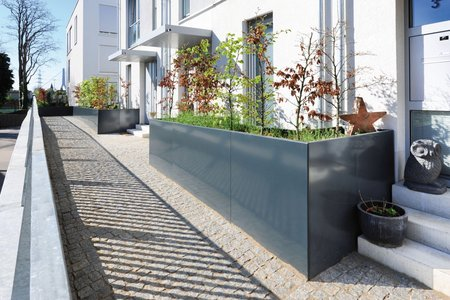 Made from aluminium and covered in an RAL 7016 plastic coating, the rectangular raised beds are 4mm thick and furnished with additional tie rods. Despite the large amounts of soil and greenery, the rods prevent the planters from buckling.