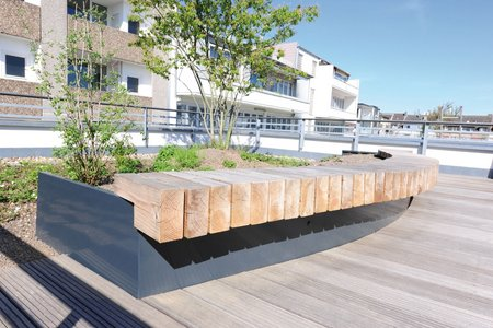 Wooden structures connected to the radial raised beds provide residents with additional seating and invite them to sit and chat to their neighbours.