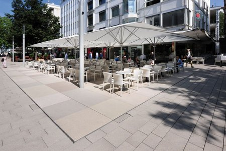 Large concrete slabs in rosé, ochre and sand shades echo the colour scheme of the pavement at Marktplatz and separate areas for shopping or dining from the pedestrian traffic.